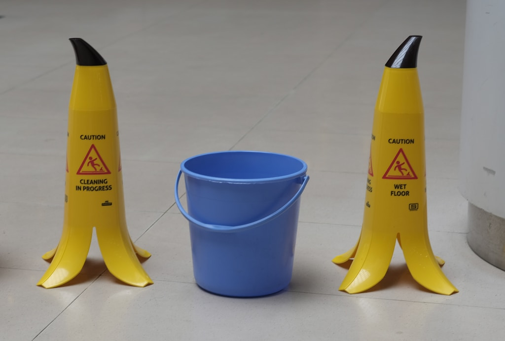 Clean school yellow and black plastic bottle beside blue plastic cup