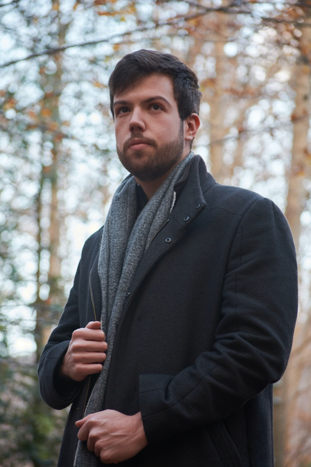 man in black coat standing near trees during daytime