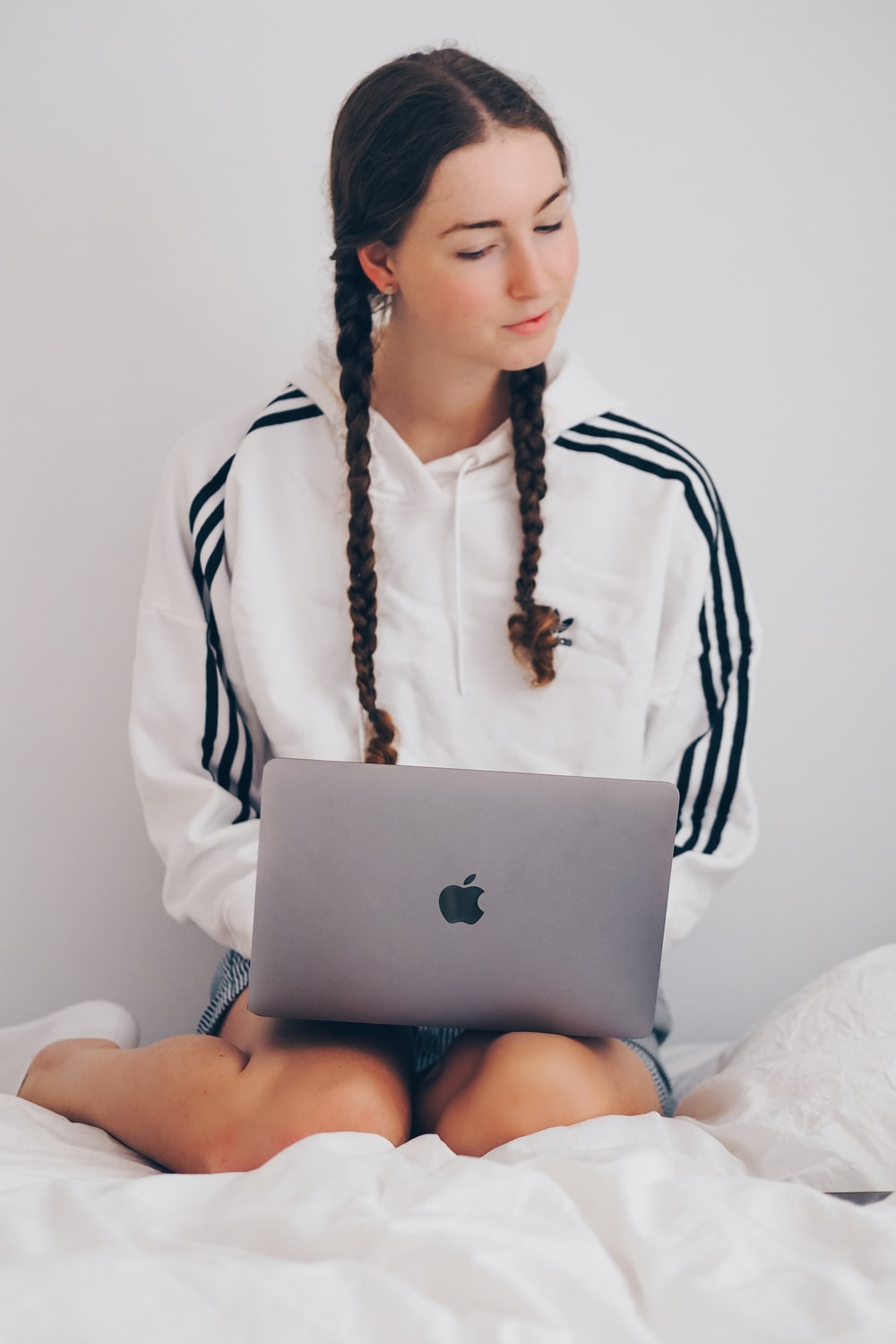 woman in white and black long sleeve shirt using silver macbook