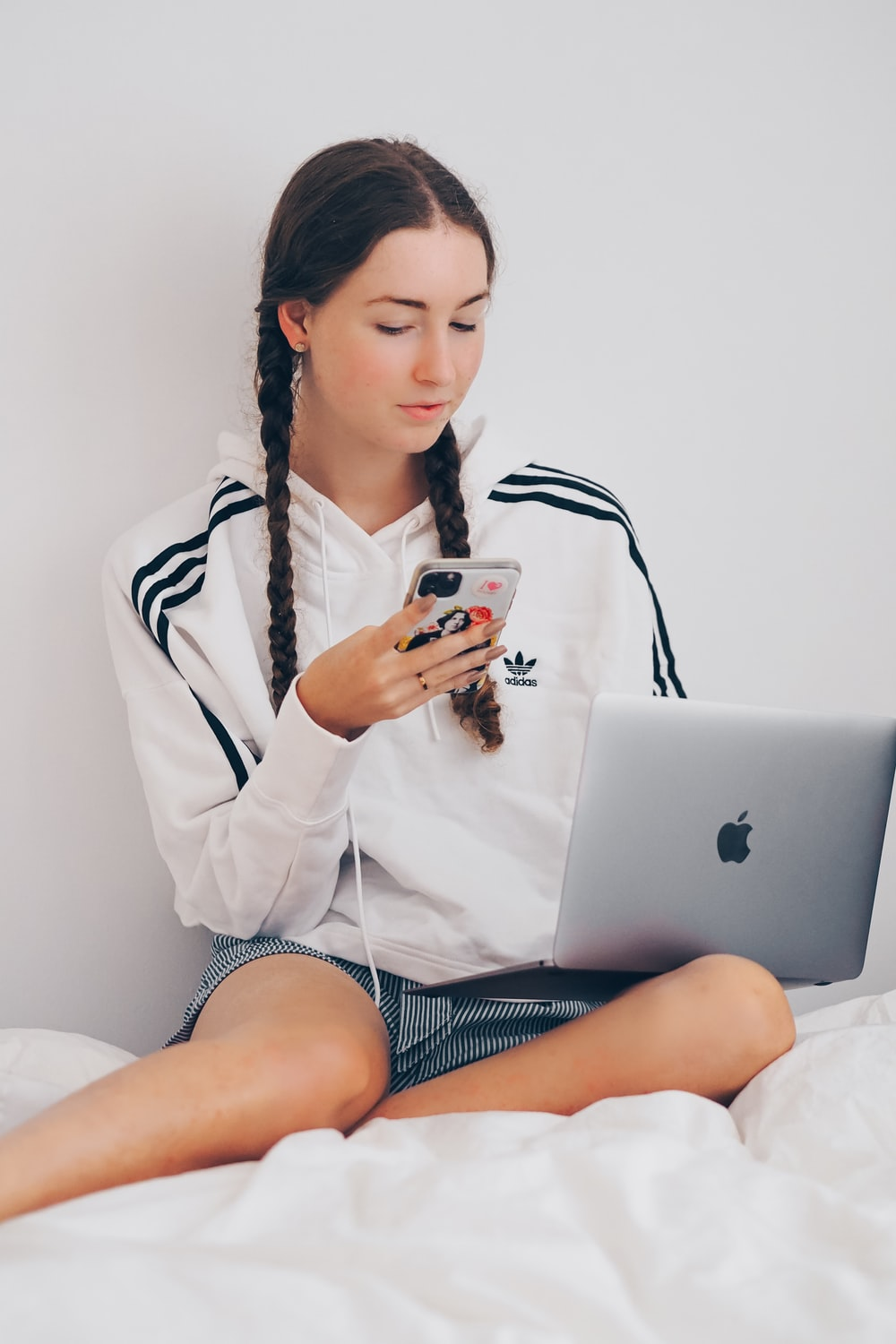 woman in white coat sitting on bed using silver macbook