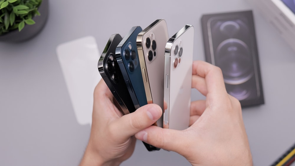 person holding white and black iphone case