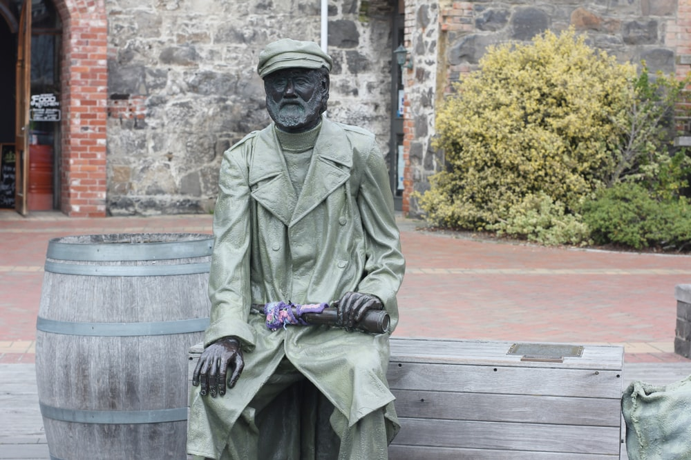 man in black leather jacket sitting on bench statue