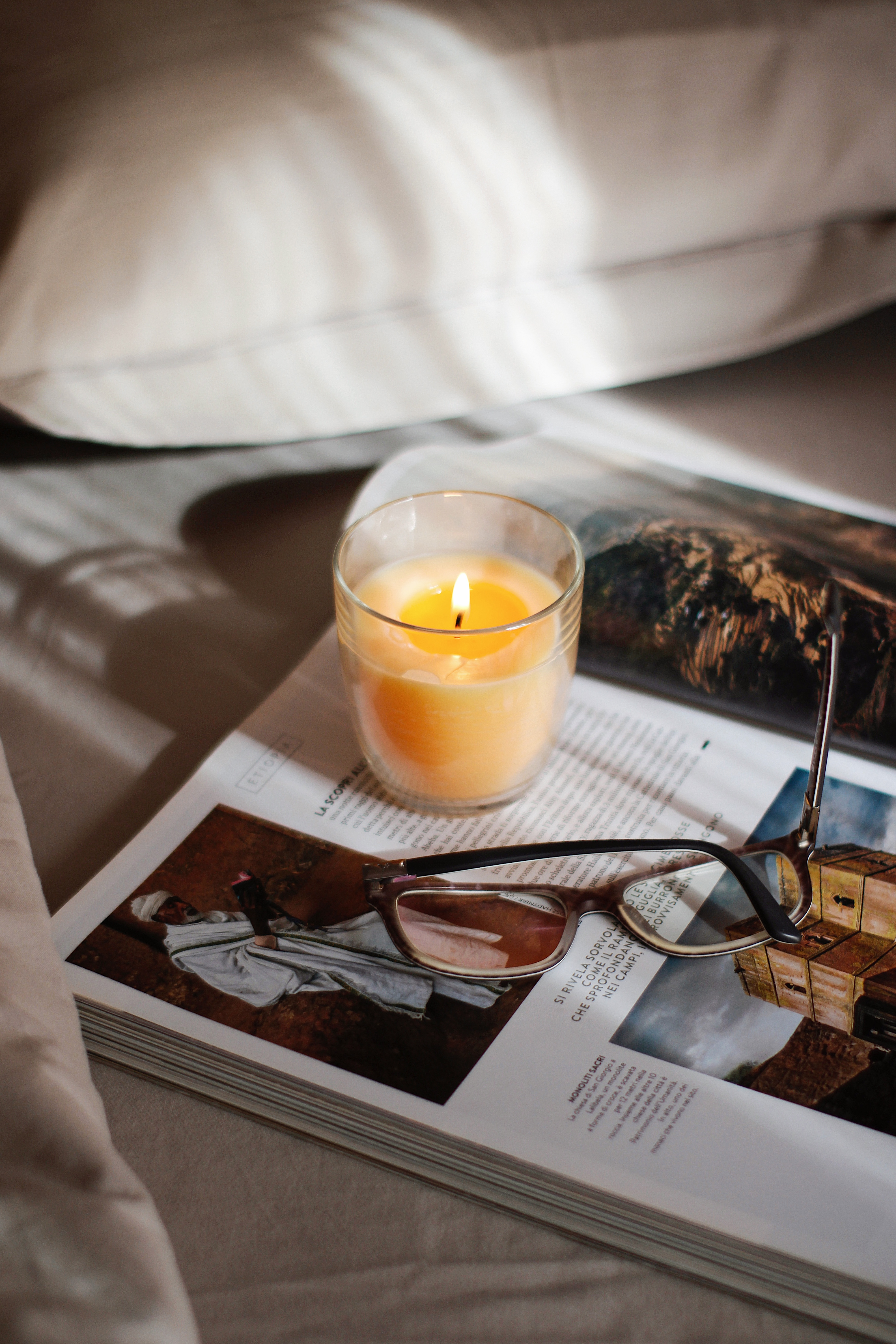 black-framed-eyeglasses-beside-clear-glass-cup-on-white-book-page