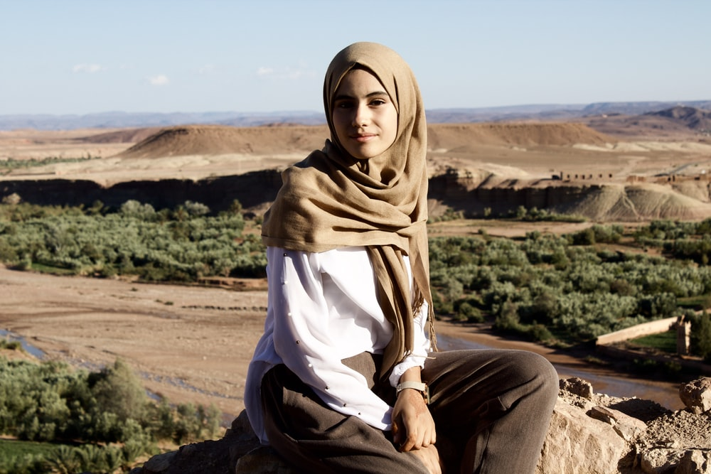 woman in brown hijab sitting on brown rock