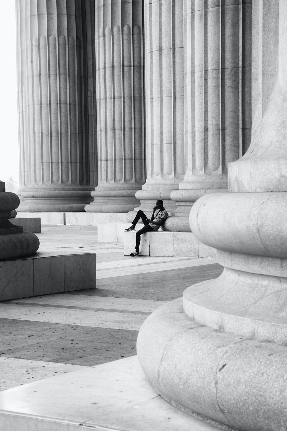 man in black jacket and pants sitting on concrete bench