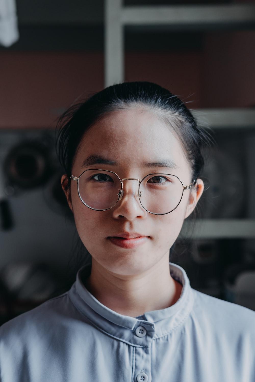 woman in white crew neck shirt wearing eyeglasses