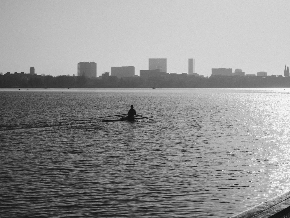 silhouette of man riding on boat on body of water during daytime