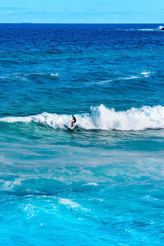man surfing on sea waves during daytime