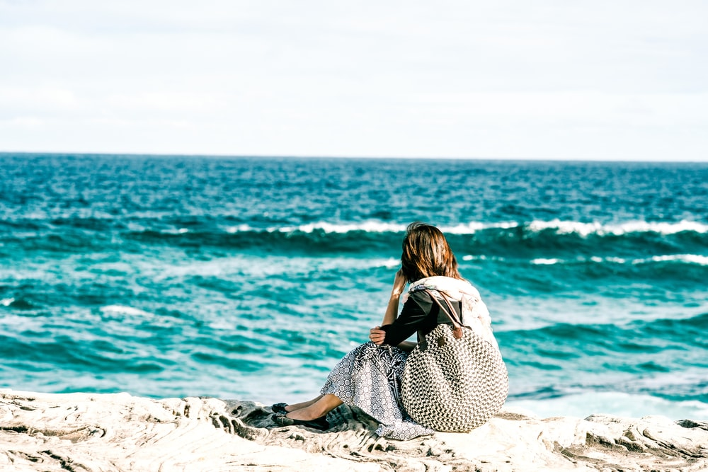 woman in black and white polka dot dress sitting on gray rock near body of water