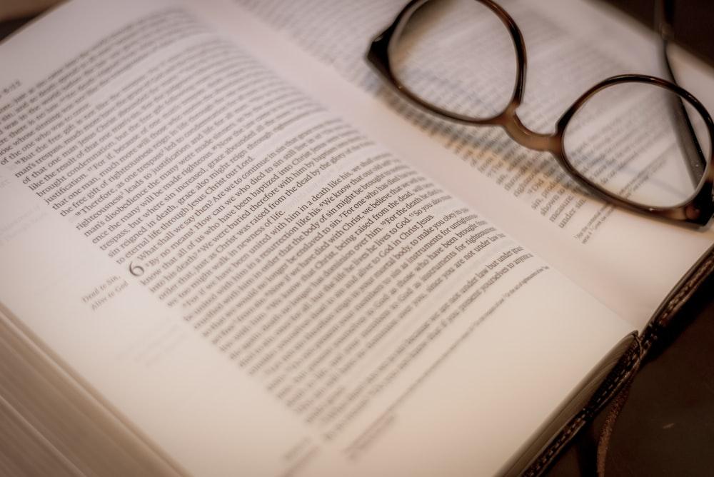 black framed eyeglasses on white book page