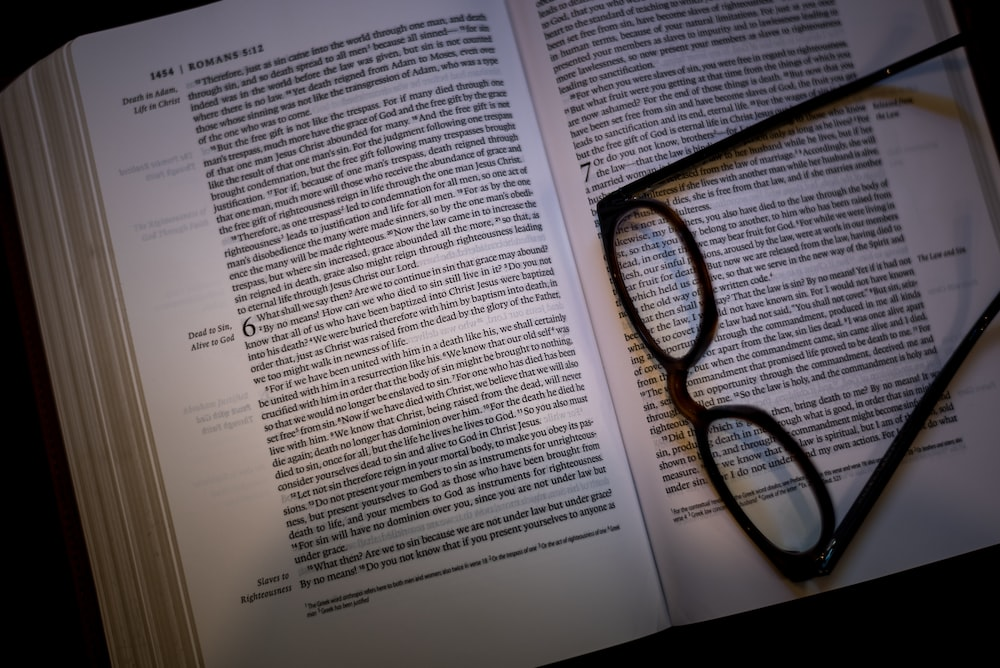 black framed eyeglasses on white book page