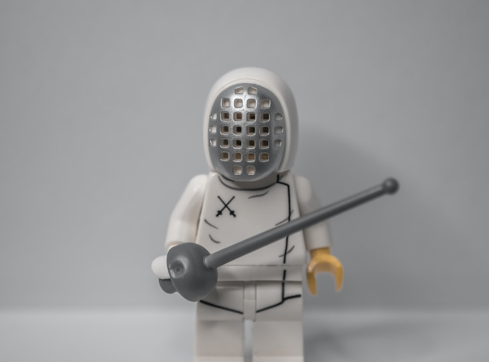 white robot toy holding a stick