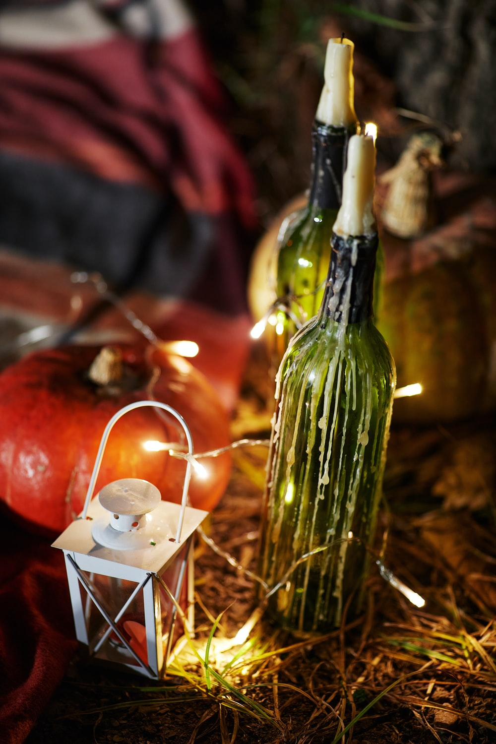 green glass bottle beside lighted candle