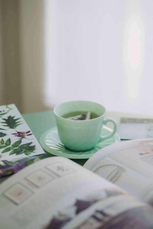 white ceramic mug on white and green floral ceramic saucer