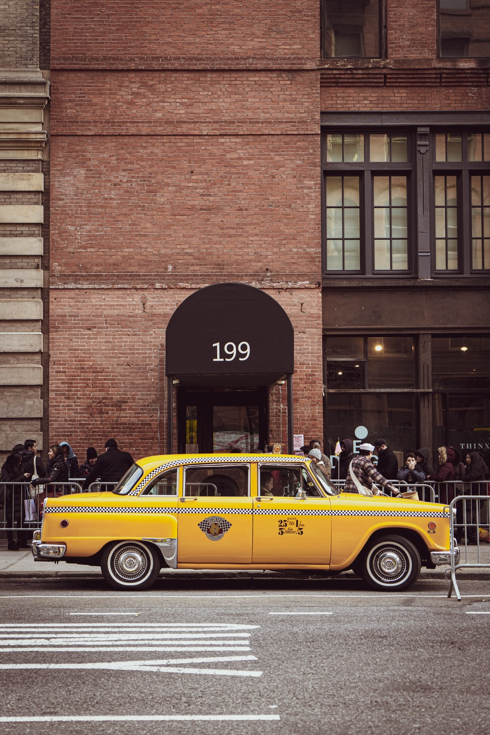 yellow taxi cab parked beside brown brick building