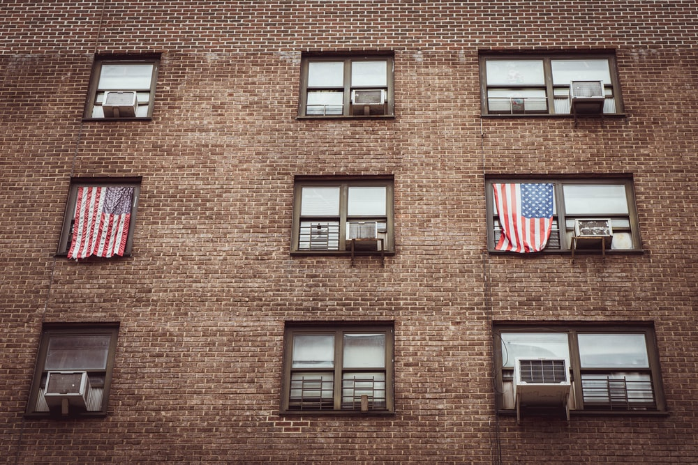 brown brick building with us flag on top