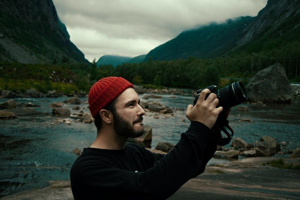 man in black sweater taking photo of green mountains during daytime