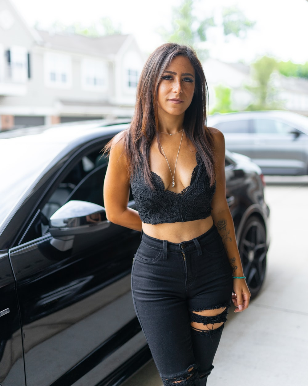 woman in black sports bra and blue denim jeans standing beside black car during daytime