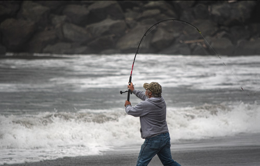 man in white shirt and blue denim jeans holding fishing rod standing on seashore during daytime
