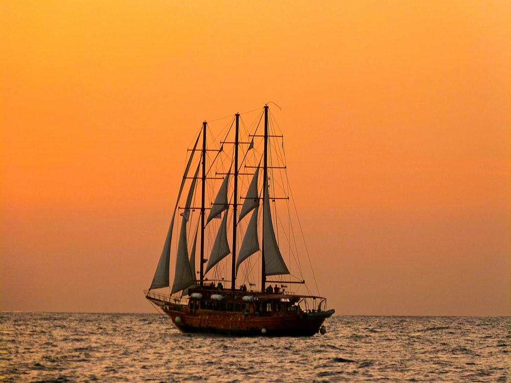 brown and white sail boat on sea during sunset