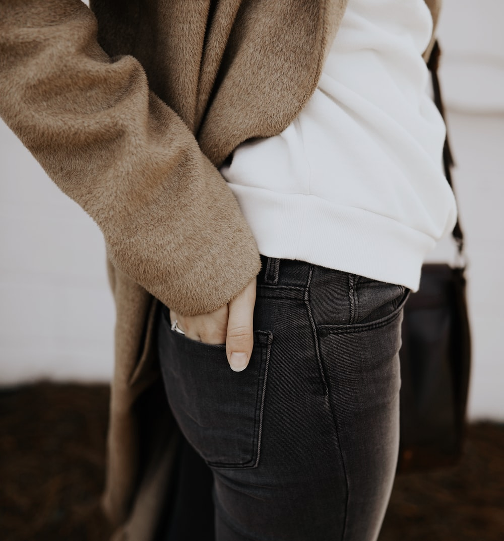 woman in brown coat and blue denim jeans