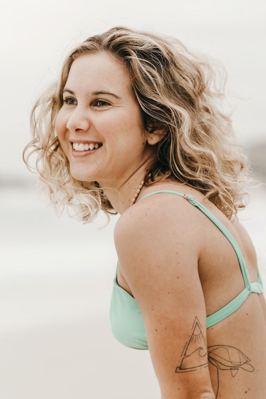 woman in teal tank top smiling