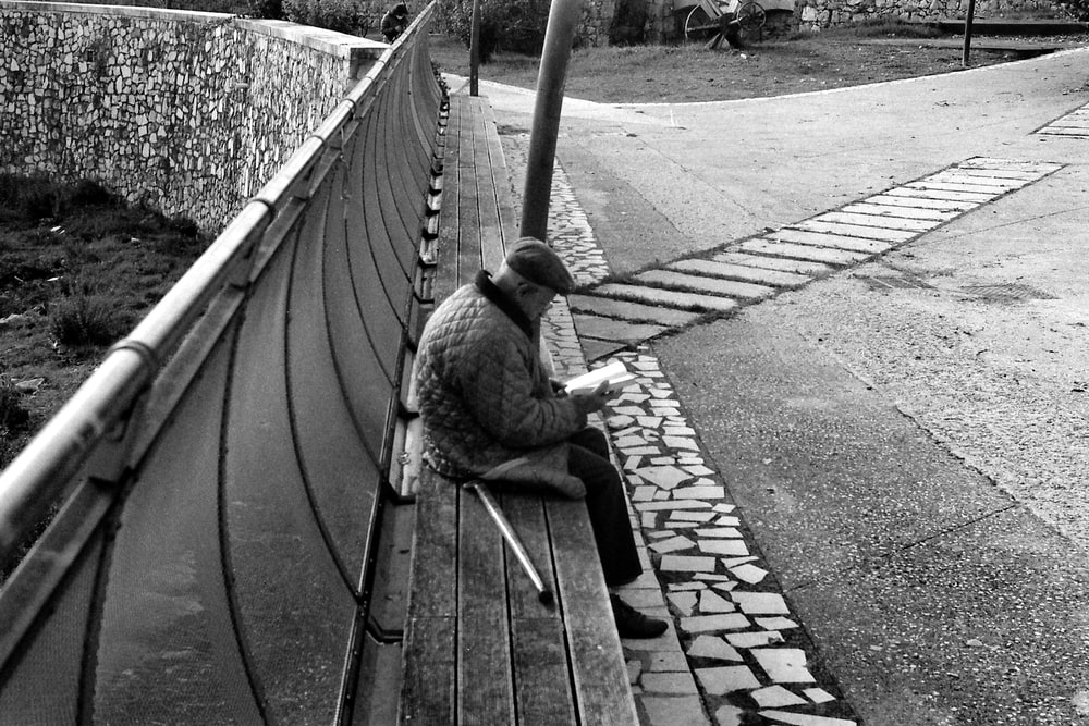 grayscale photo of man sitting on wooden bench