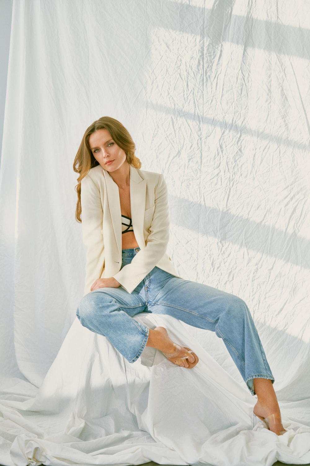 woman in brown blazer and blue denim jeans sitting on white textile