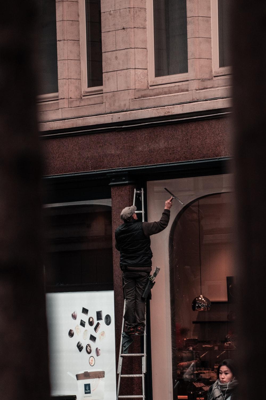 man in black jacket and black pants standing beside brown brick wall