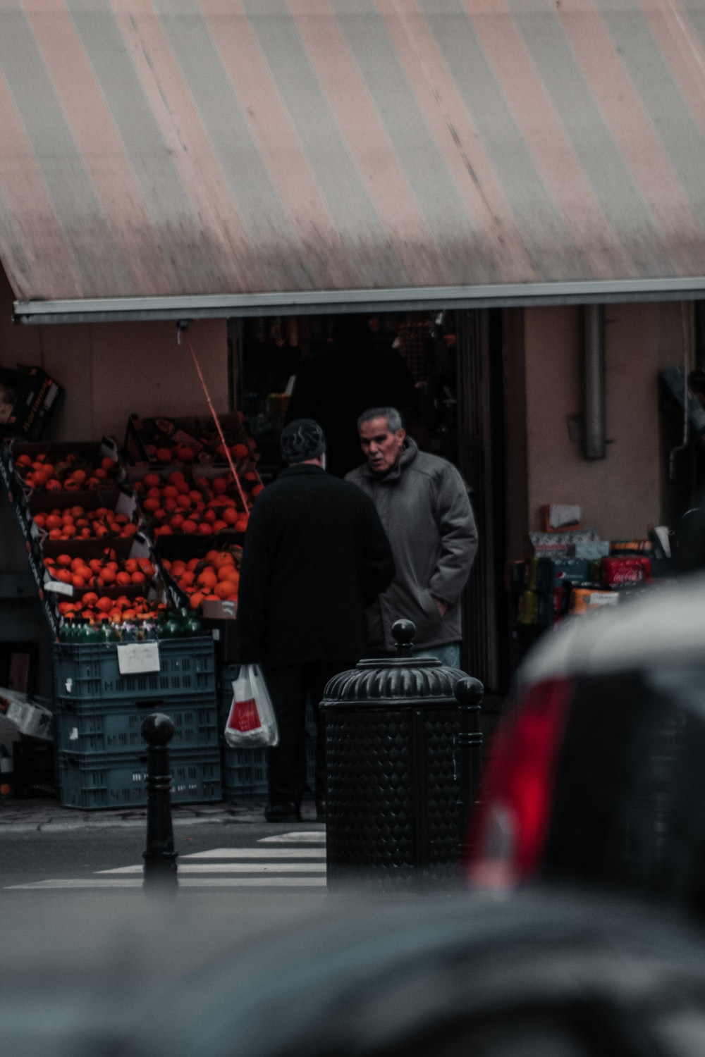 man in black jacket standing near fruit stand during daytime