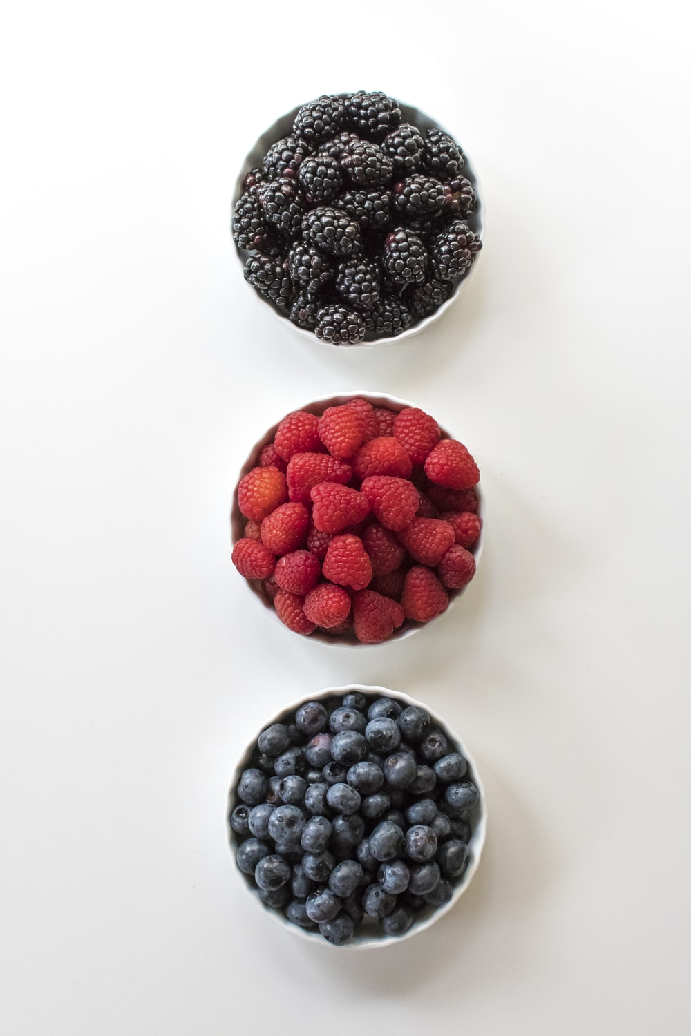 red and black berries on white surface