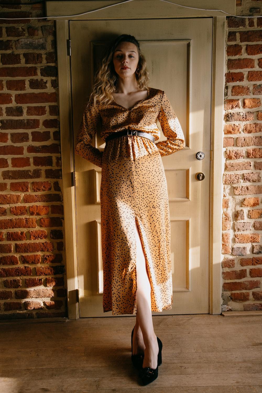 woman in brown long sleeve dress standing beside brown brick wall