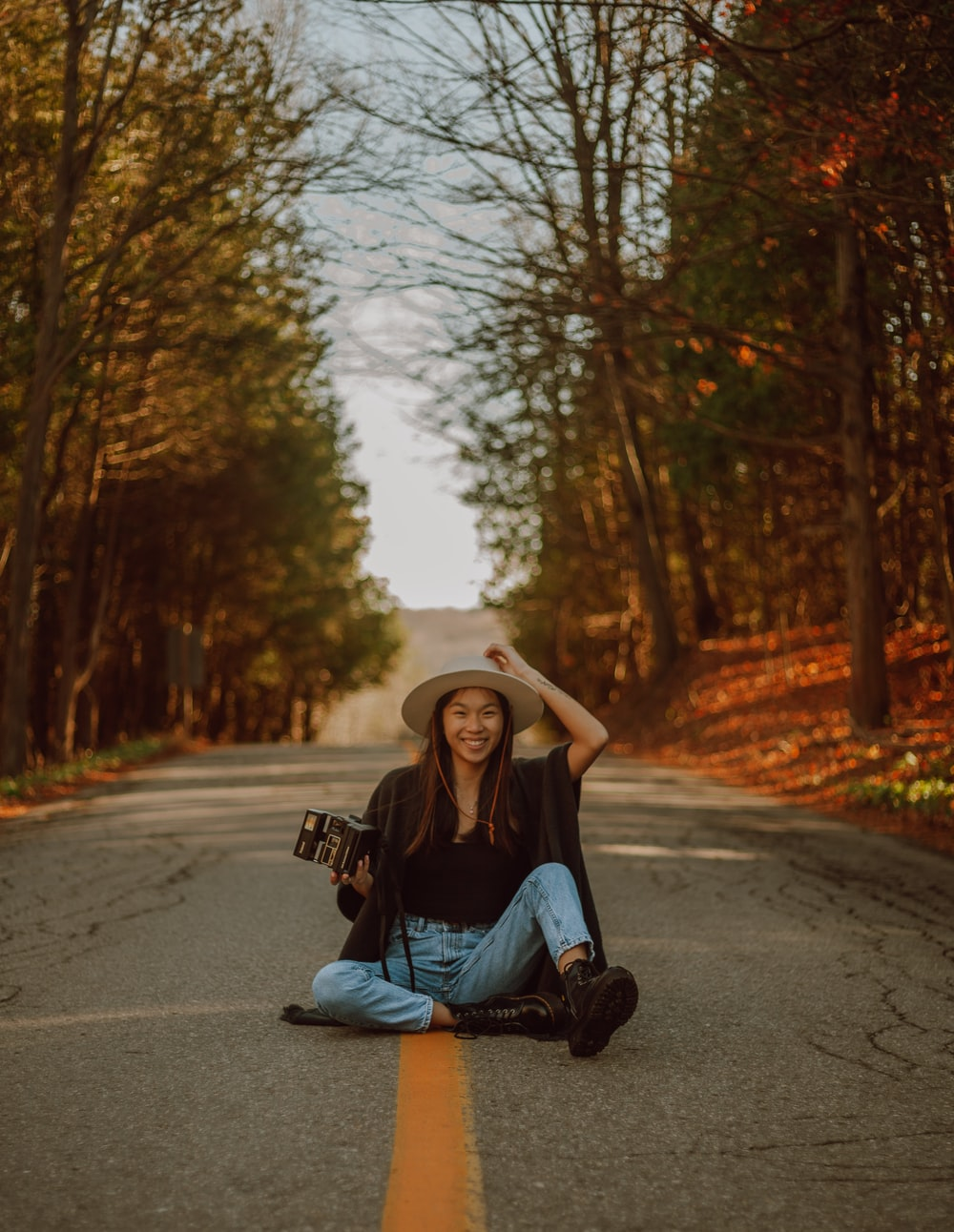 woman in black shirt and blue denim jeans sitting on road during daytime