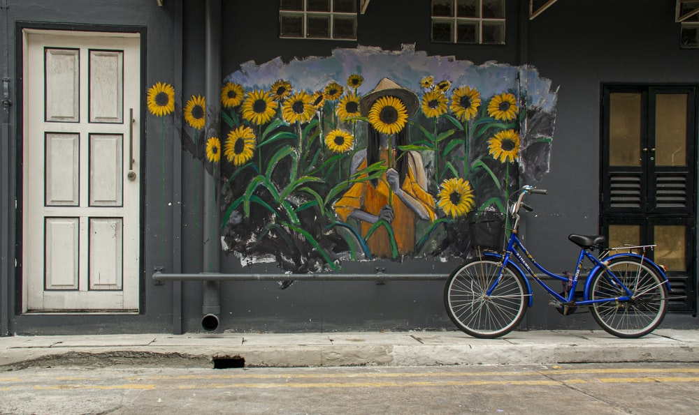 blue bicycle parked beside blue and yellow floral wall