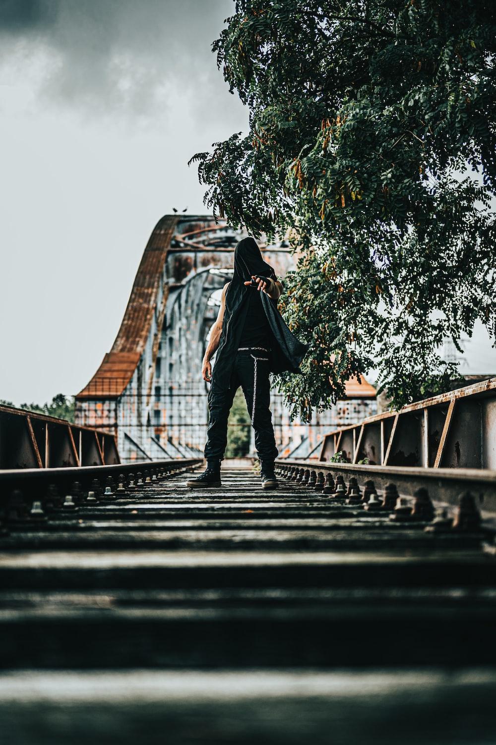 woman in black jacket standing on bridge during daytime