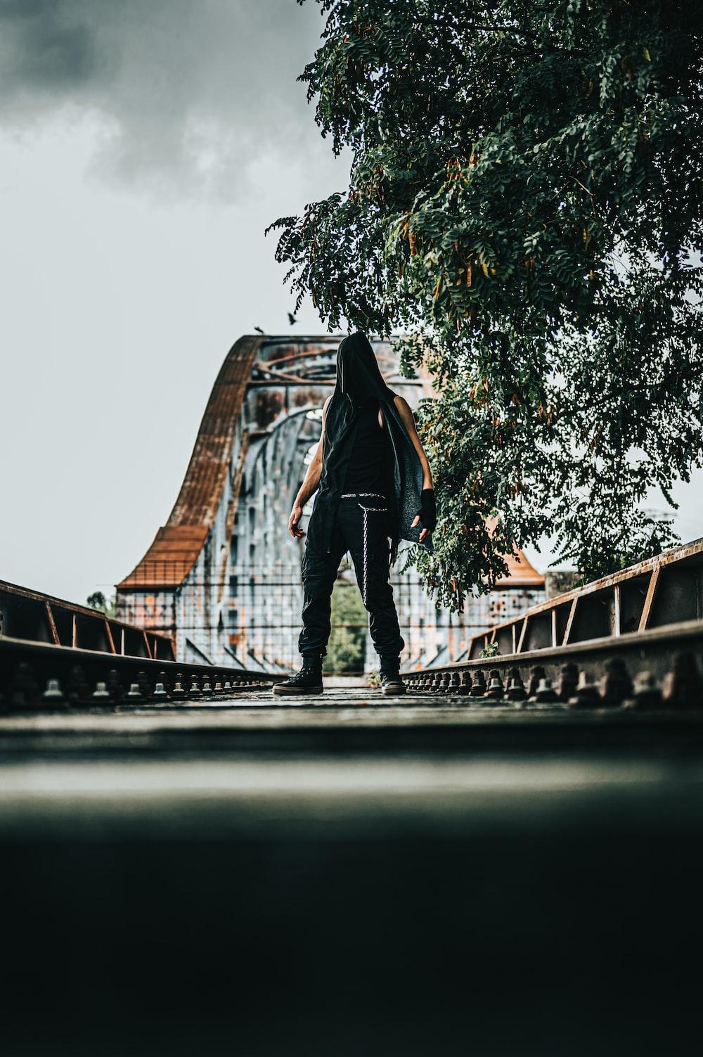 man in black jacket and black pants standing on bridge during daytime