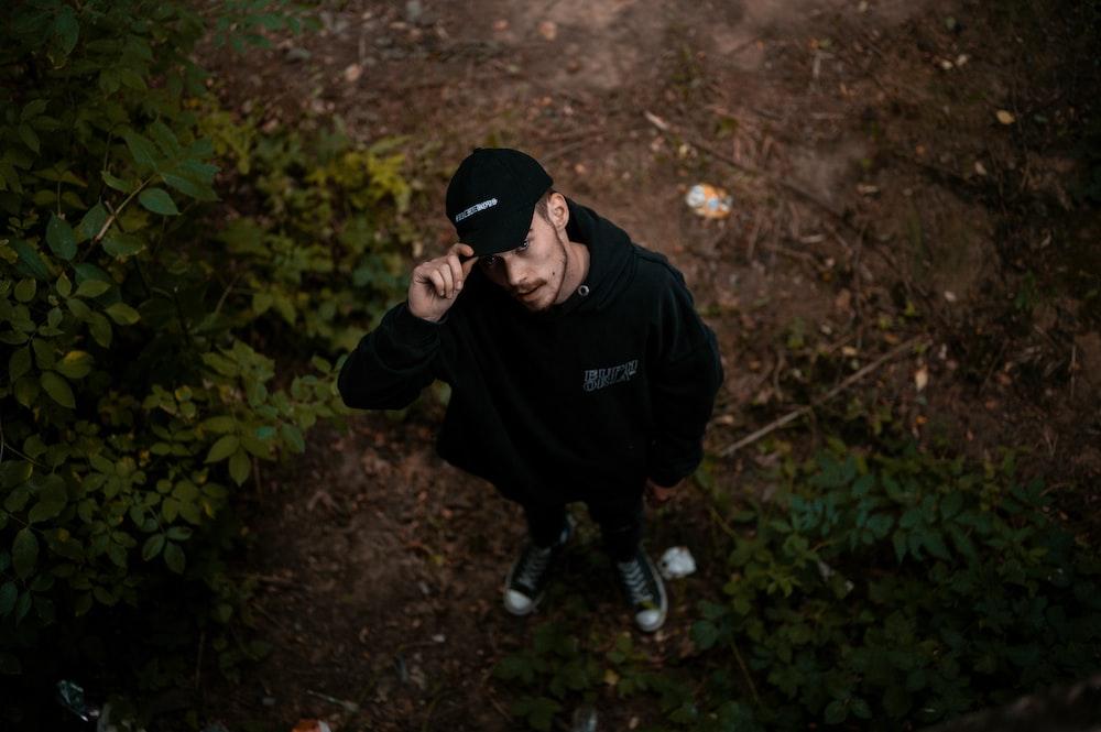 man in black hoodie and black pants sitting on ground