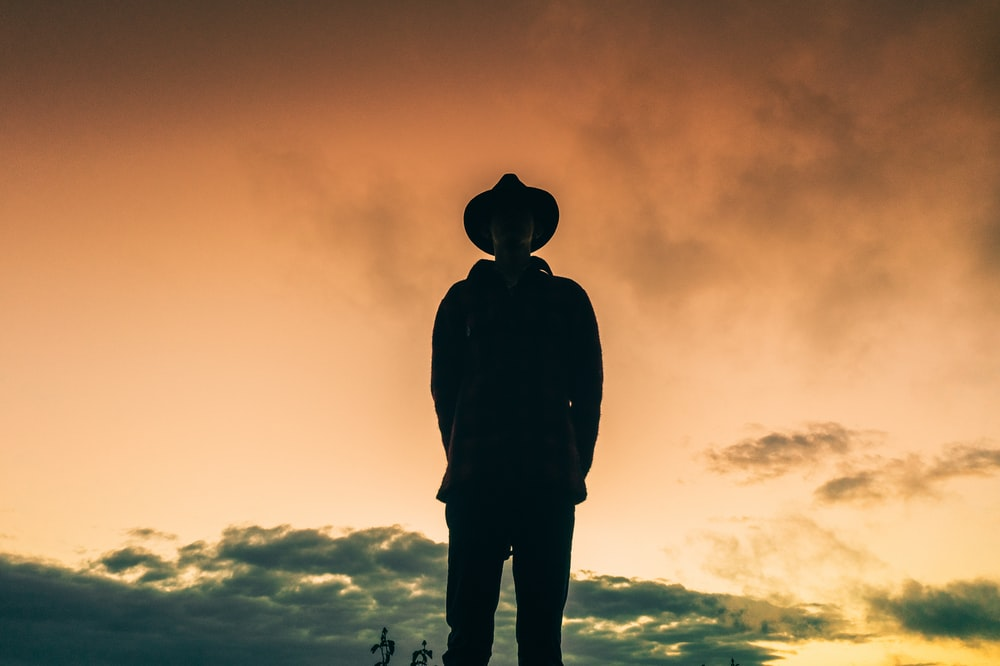silhouette of man wearing hat and jacket