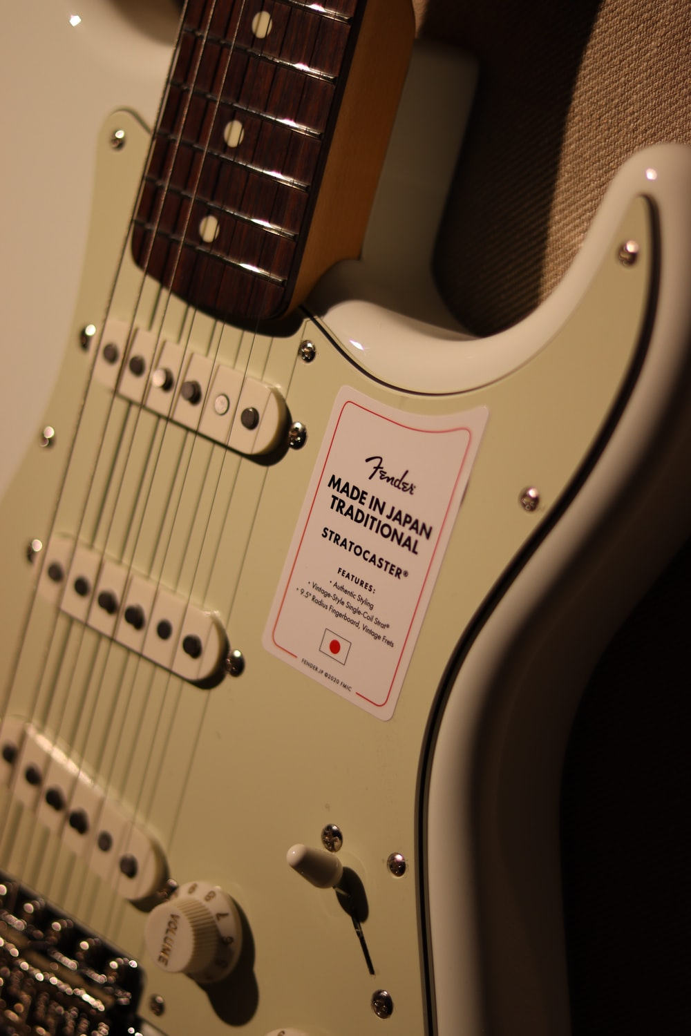 white and red stratocaster electric guitar