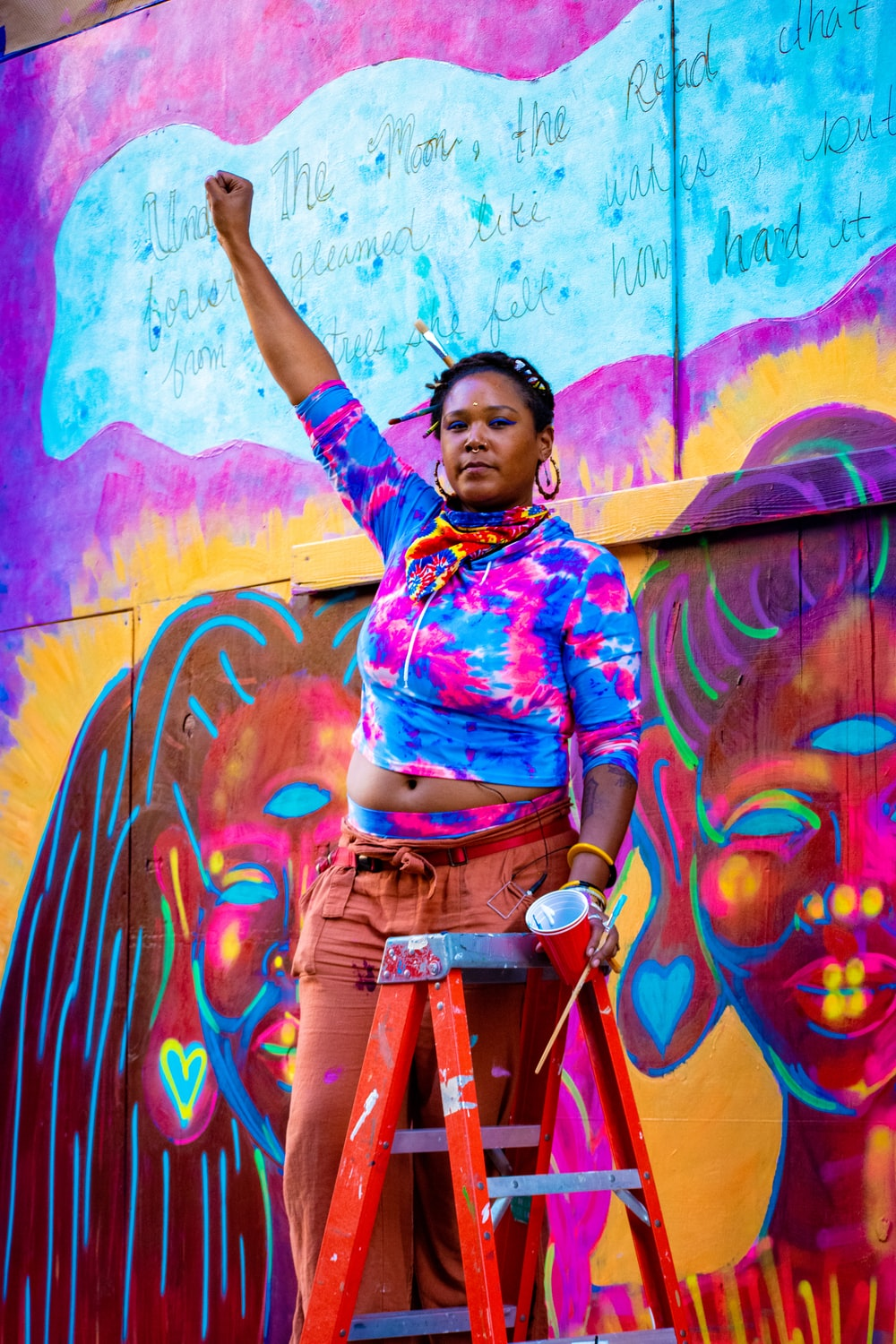 woman in blue and pink floral button up shirt and brown pants standing beside graffiti wall