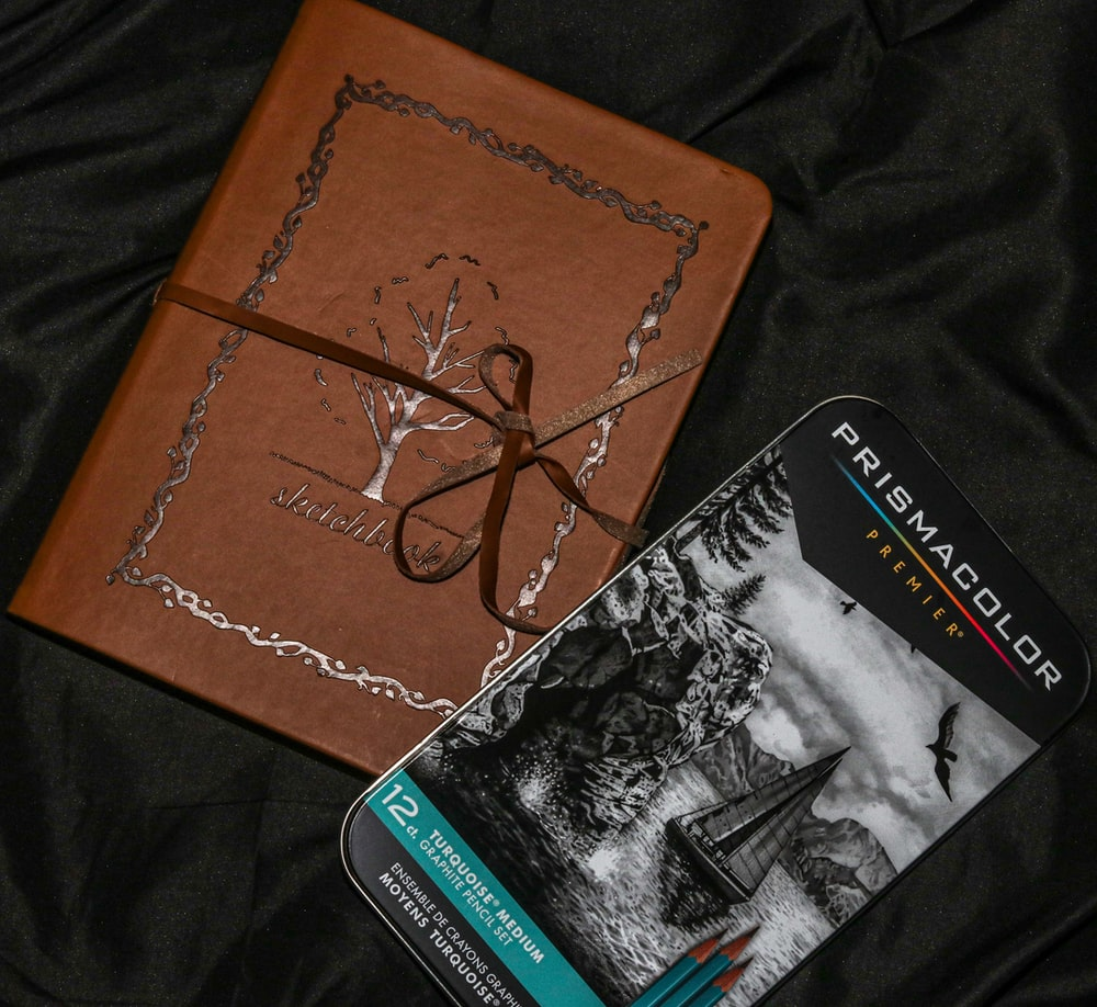 brown and black book on black textile