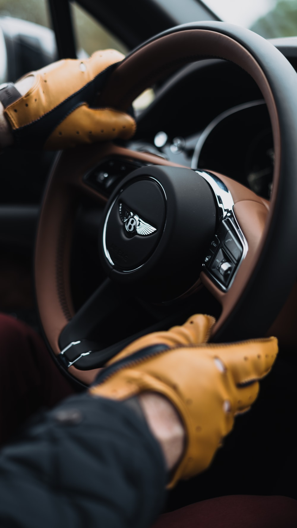 person holding black and silver nissan steering wheel