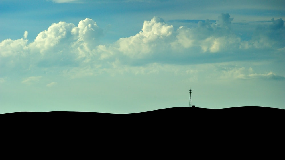 silhouette of person standing on hill under white clouds and blue sky during daytime
