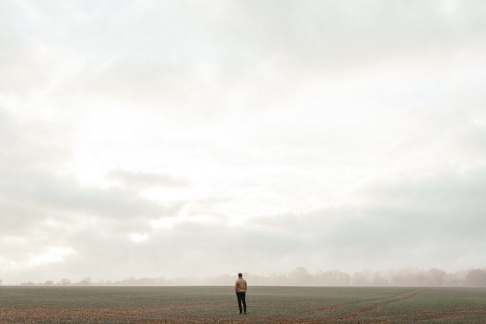 man in black shorts standing on brown field under white cloudy sky during daytime