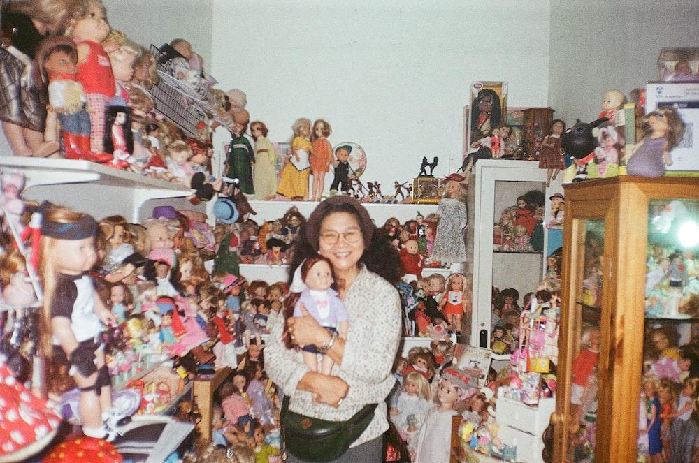 girl in white sweater standing beside plush toys