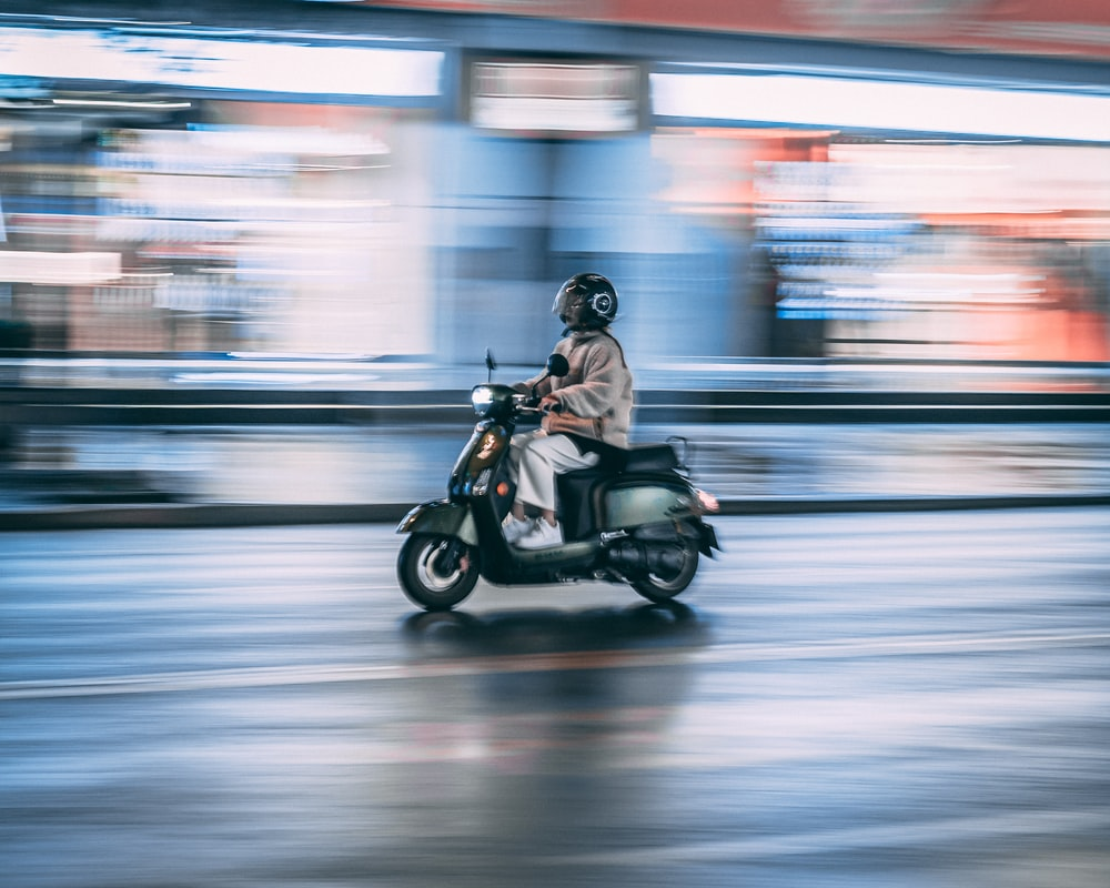 man riding motorcycle in time lapse photography