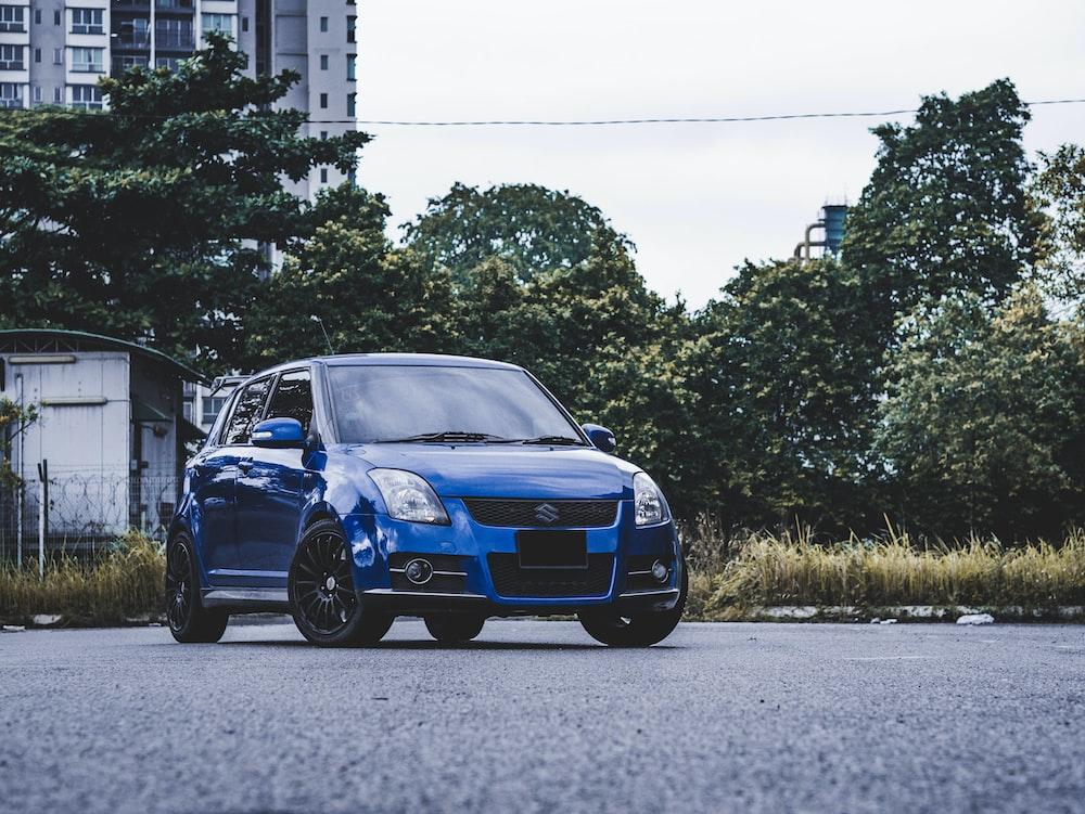 blue bmw m 3 parked on gray asphalt road during daytime