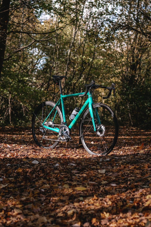 green and black mountain bike on dirt road