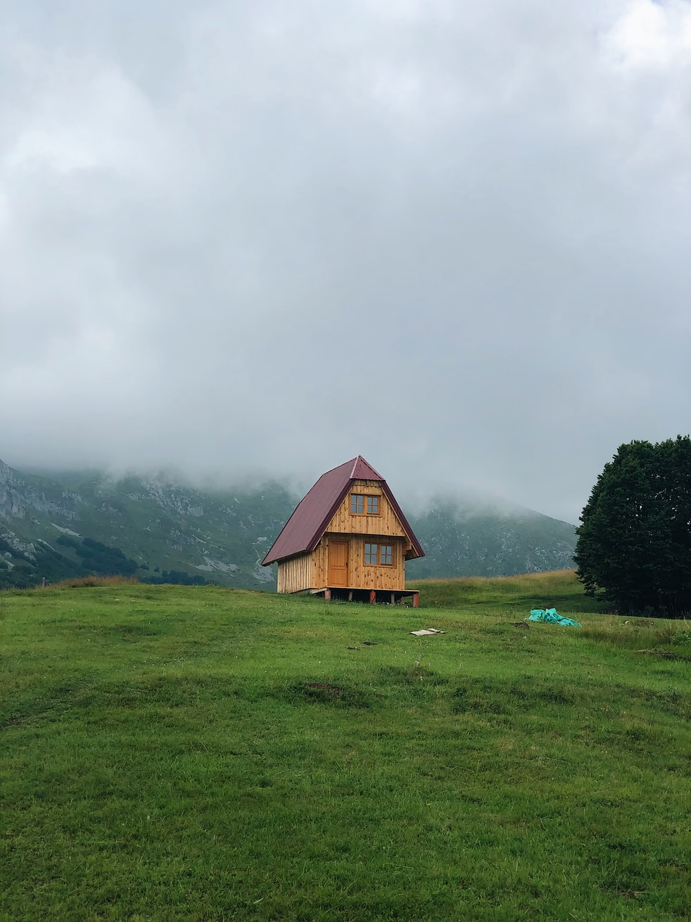 brown wooden house on green grass field near green mountains under white clouds during daytime