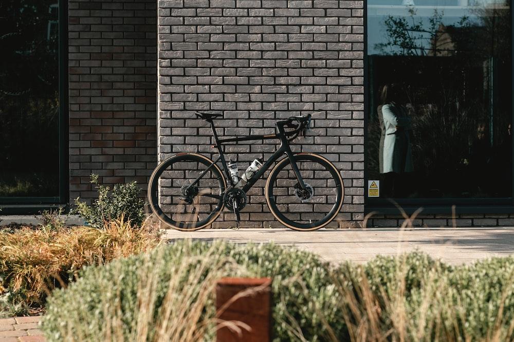 black and gray mountain bike beside brown brick wall